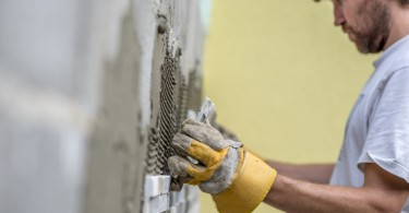 Builder tiling a concrete wall with decorative ornamental tiles lining up a tile with his gloved hands to seat into the tiling cement on the wall, profile view along the length of the wall.